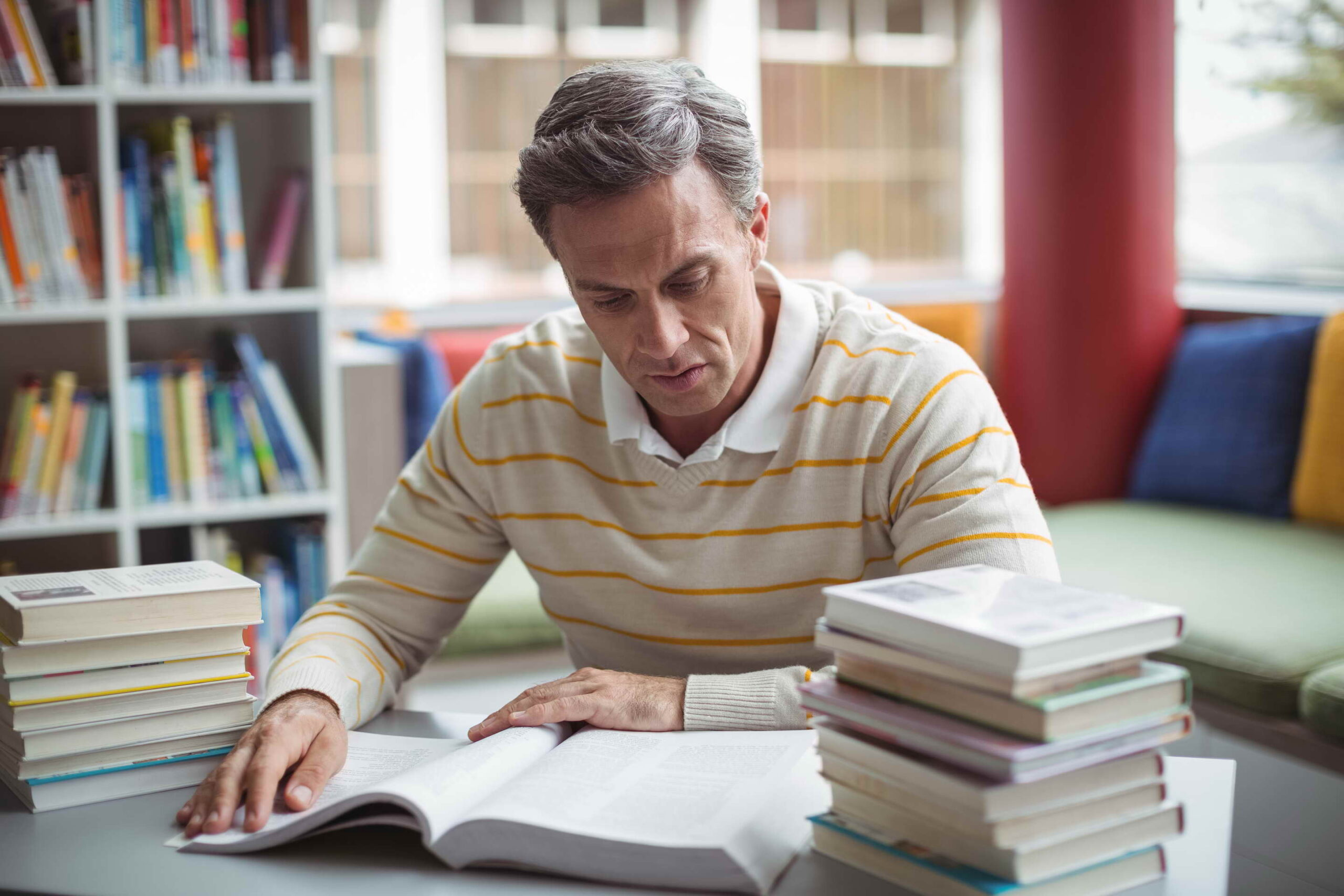 Attentive school teacher reading book in library at school
